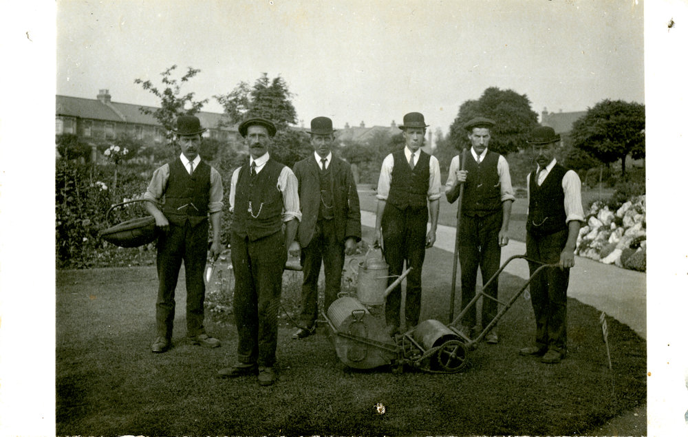 Six gardeners pose in a public park, proudly holding their tools including a watering can, trug and lawnmower - about 1910