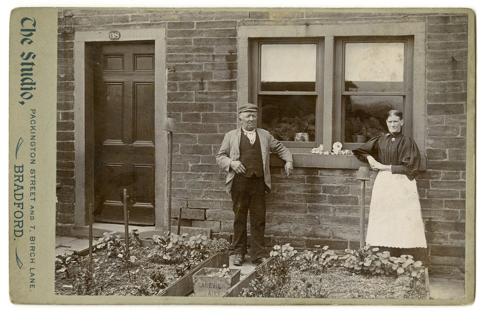 In a front garden on Manchester Road, Bradford, a man and woman pose by two raised beds and a window lined with ferns. This photograph was taken by E. Cole Keighley in about 1900.
