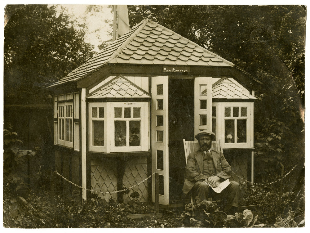 Sitting on a deckchair, a man poses outside the doors of a summerhouse surrounded by bard-edged beds with flowers and vegetables - about 1910.