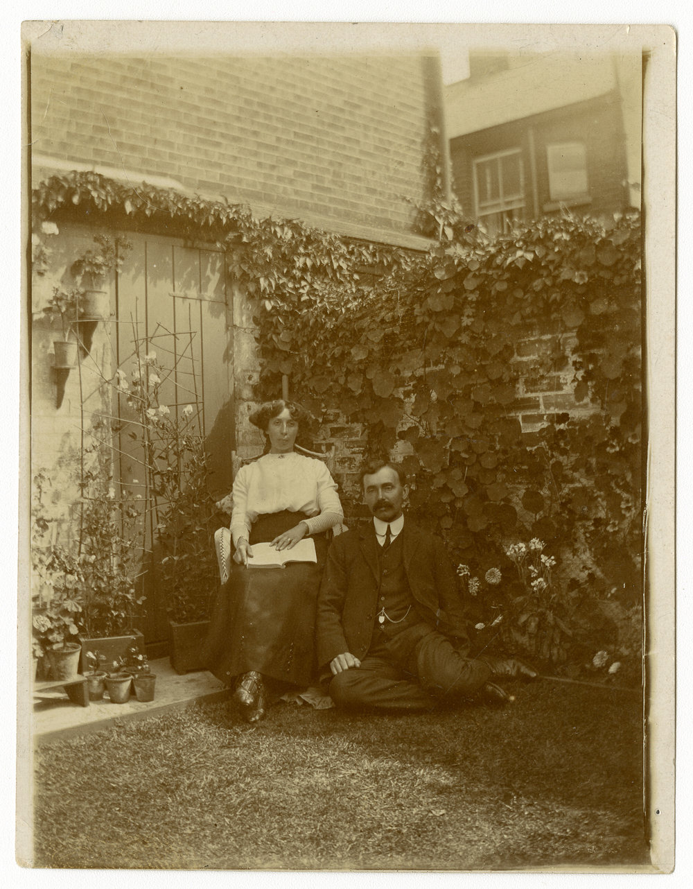 A couple pose seated in a shaded corner of a back garden in Cobham, Norfolk , surrounded with climbing plants and a well kept lawn -about 1910