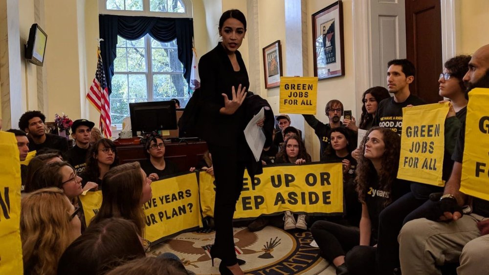 Rep. Alexandia Ocasio-Cortez speaking to Green New Deal supporters in House Speaker Nancy Pelosi's office (Photo Credit: ABC News)