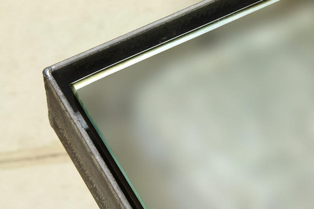Steel float frame hosting a mirror