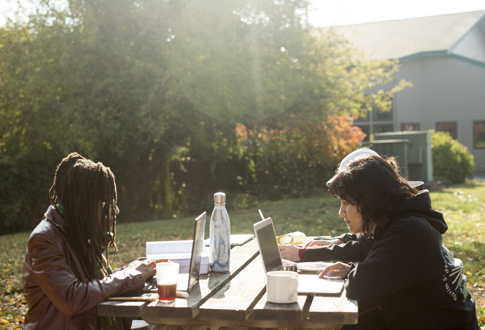 women-on-computers-outside-at-picnic-table