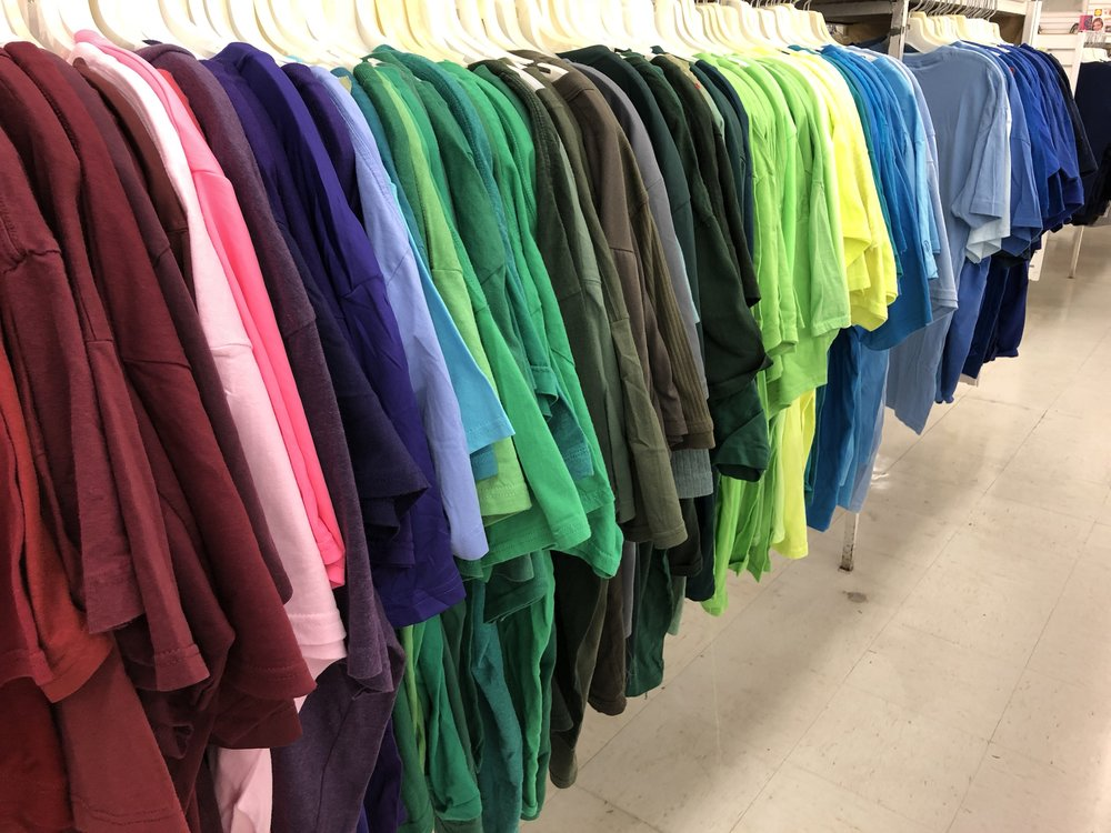 An array of t-shirts organized by color.