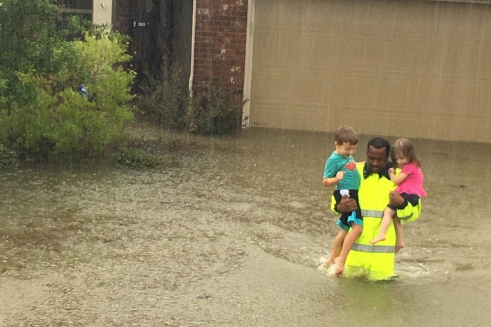 Volunteer helps bring children to safety in Houston flood.