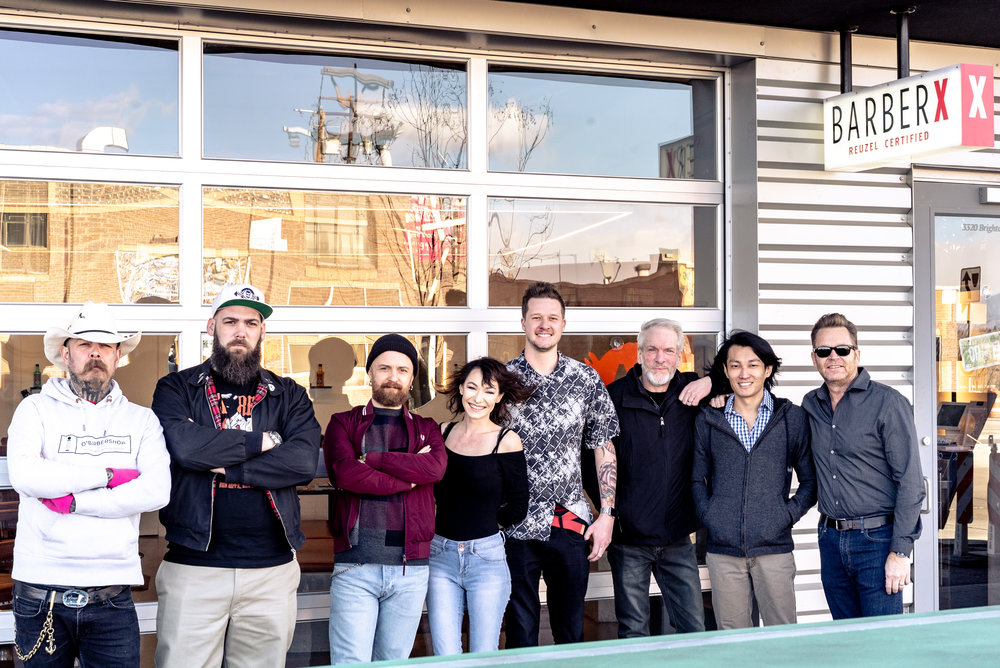 BarberX  receives special guests (from left to right),  Reuzel  co-founder, Bertus (his business partner, Leen, could not join this time),  Schorem Haarsnijder & Barbier  shop manager, Miky,  Old School Barber Academy  manager, Nelis,  BarberX  barbers, Anya and Brady, owners, Bruce and Carl, and  Reuzel  co-founder and CEO, Rob Wilcox. Photo taken by  Schorem Haarsnijder & Barbier  resident photographer, Jelle, in front of BarberX located in Denver's RiNo Art District.
