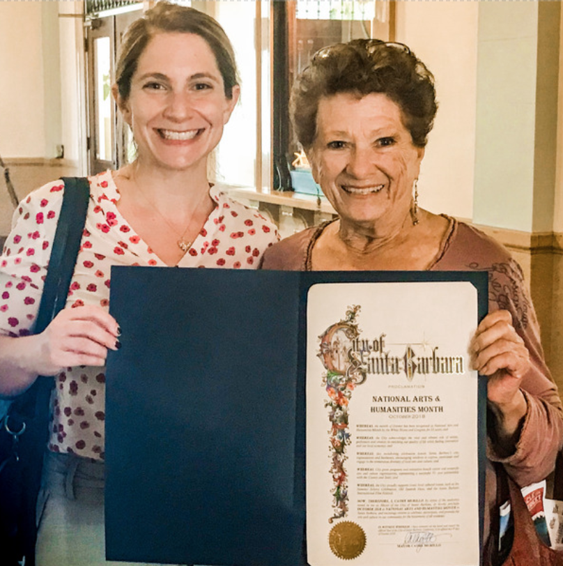 Sarah York Rubin, Executive Director of Santa Barbara County Office of Arts & Culture giving the City of Santa Barbara Proclamation of National Arts & Humanities Month to Julie McLeod, Founder of AWoL.