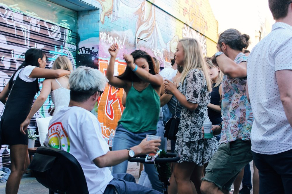Image of several people dancing at an outdoor party in a laneway. One of the party people uses a mobility scooter.