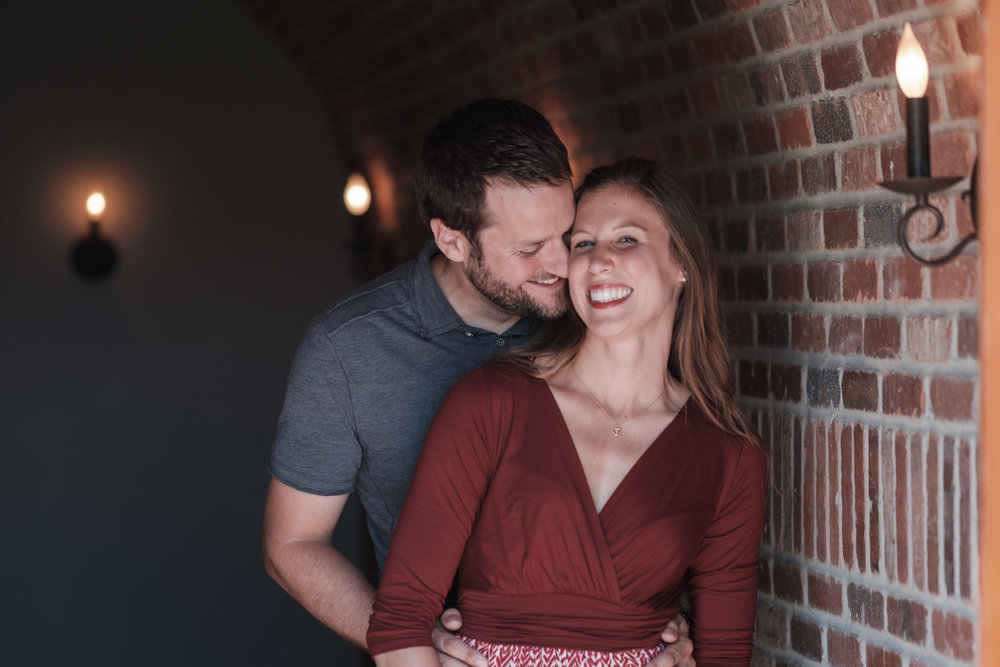 Couple laughs and smiles inside the Copperstone Inn at The Pavilion at Orchard Ridge Farms during an engagement session
