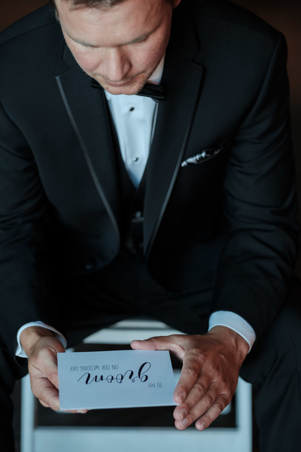Groom reading letter from his bride before wedding begins with window light while dressed in his suit and bow tie.