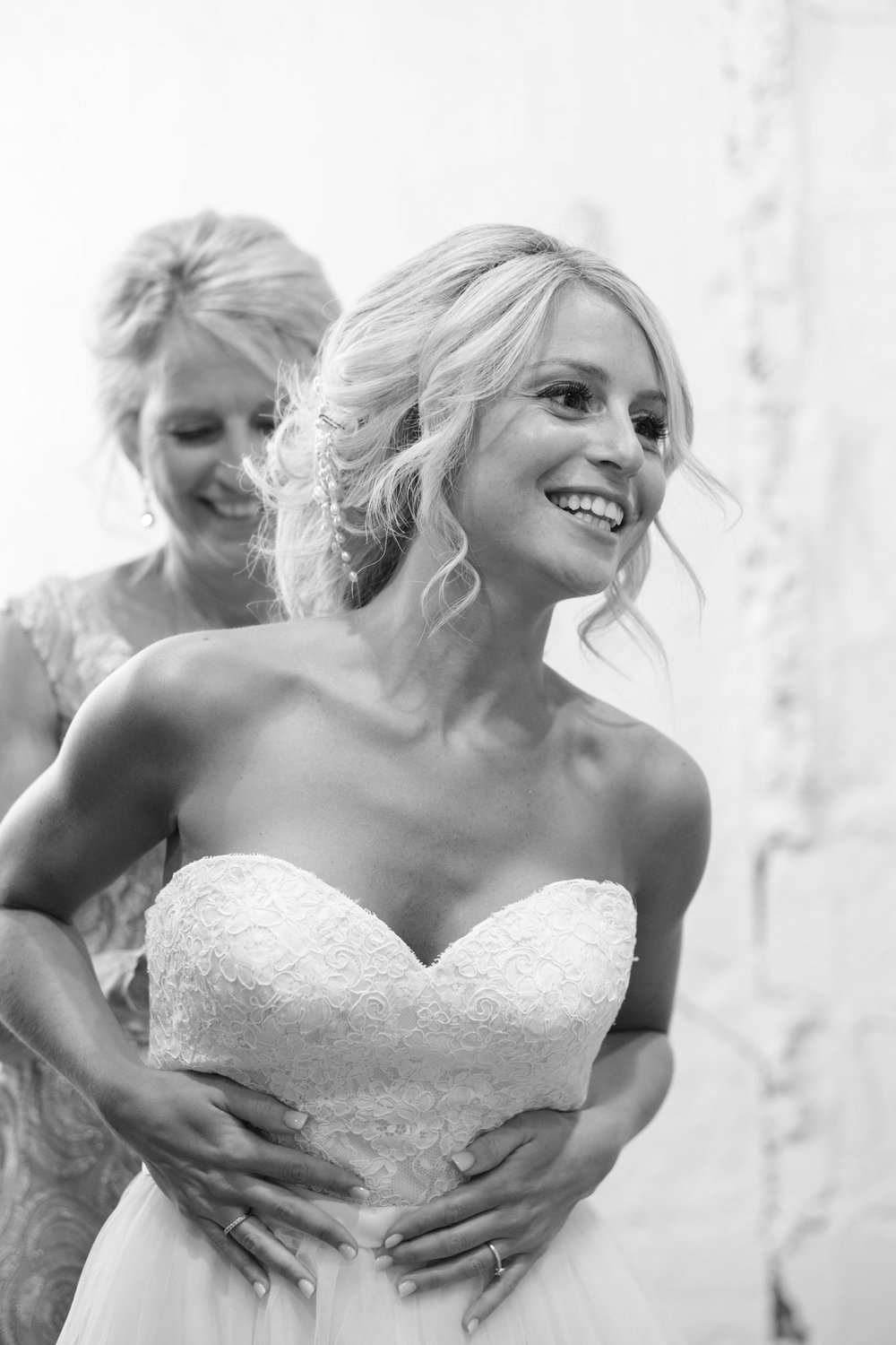 Bride smiling while holding dress on as mom finishes tying it up in the bride room at prairie street brewhouse in rockford illinois