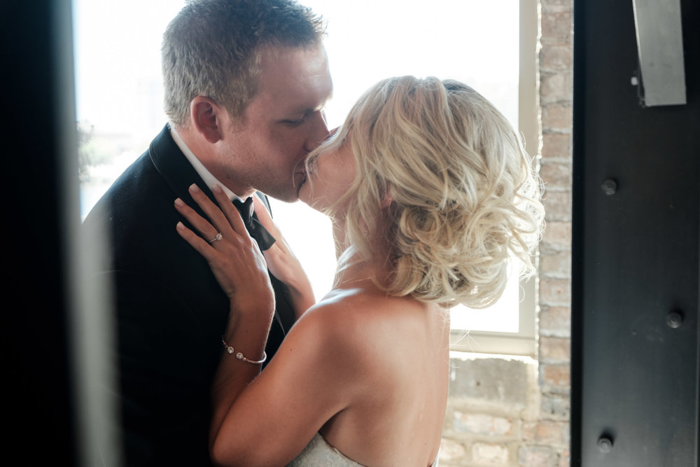 Bride and groom embrace and kiss during their first look at PSB in Rockford, Illinois