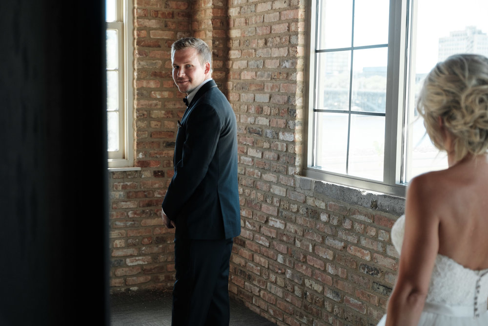 The moment the groom turns to see his bride at their first look at Prairie Street Brewhouse in Rockford, Illinois