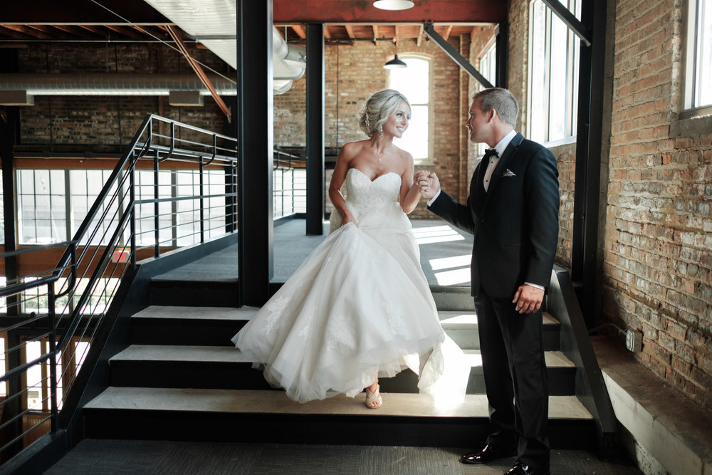 Bride and Groom walking down stairs smiling at each other at Prairie Street Brewhouse in Rockford, Illinois.