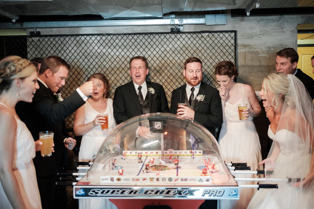 Bride and groom playing bubble hockey while wedding party cheers them on at Dock Side Bar in Prairie Street brewhouse in Rockford, Illinois.