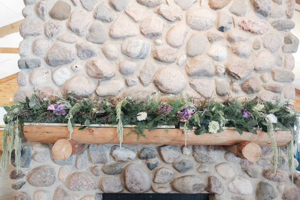 Fireplace mantle covered in flowers at WIlliams Tree Farm wedding in Roscoe Illinois