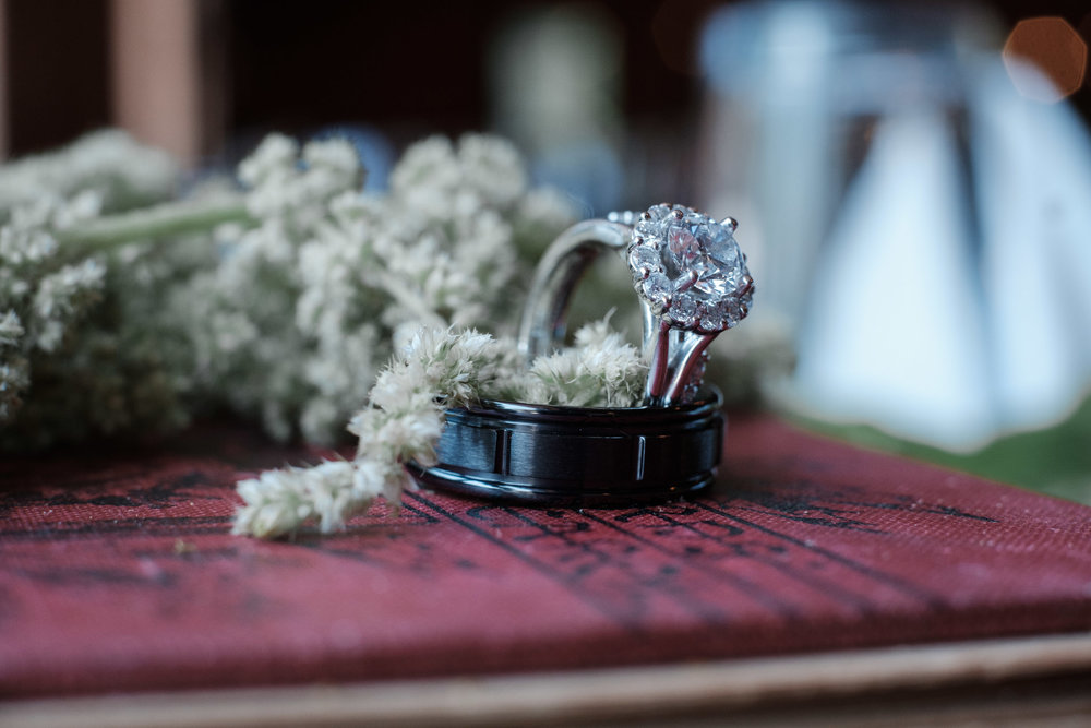 Photo of wedding rings with flowers resting on books at WIlliams Tree Farm wedding in Roscoe Illinois