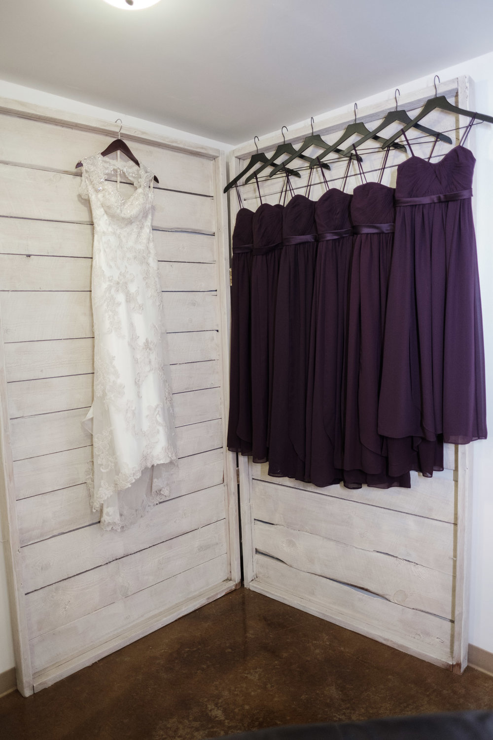 Bride and bridesmaid dresses hanging on shiplap wall at WIlliams Tree Farm wedding in Roscoe Illinois
