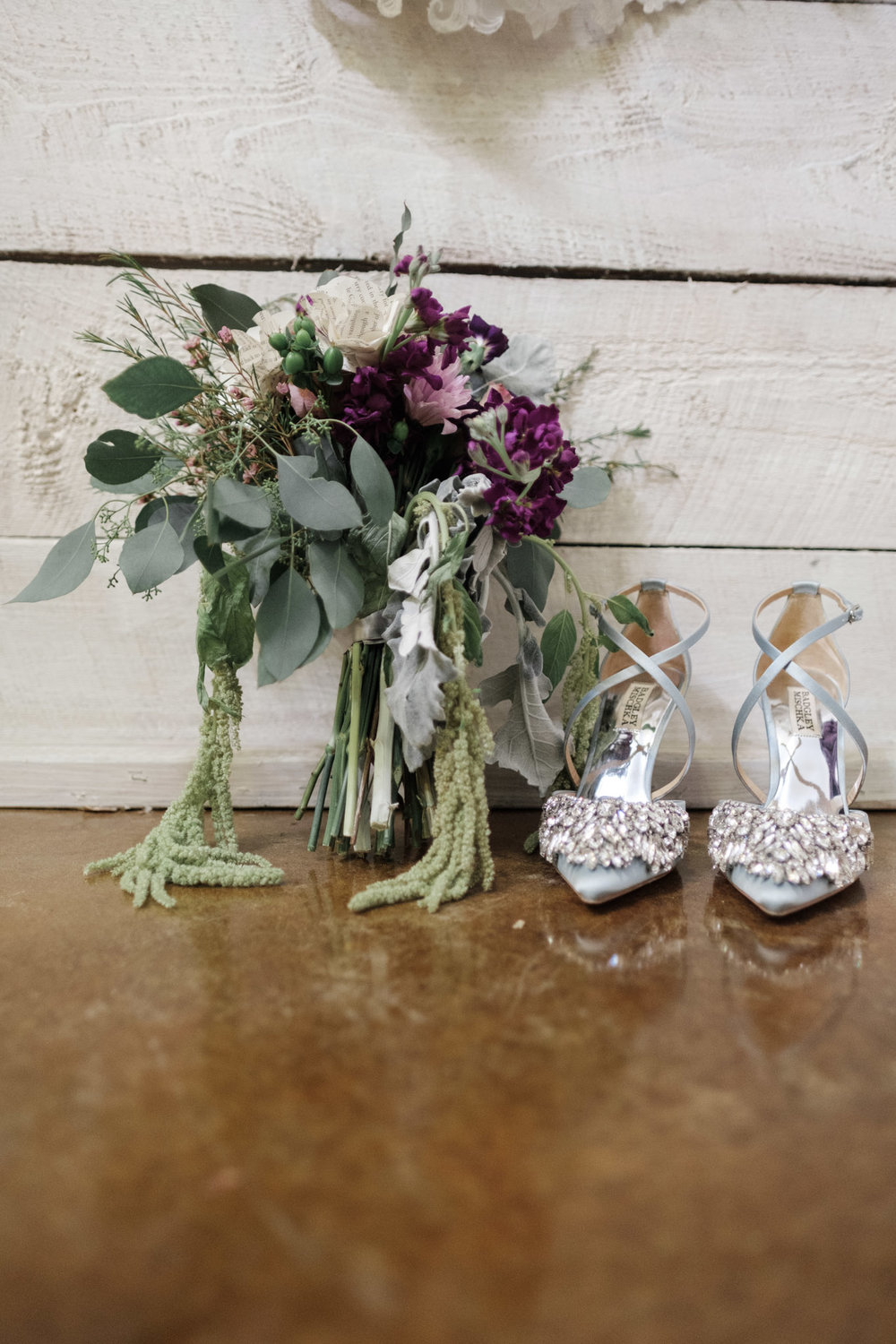 Bridal flowers and blue sparkly shoes against white shiplap wall at WIlliams Tree Farm wedding in Roscoe Illinois