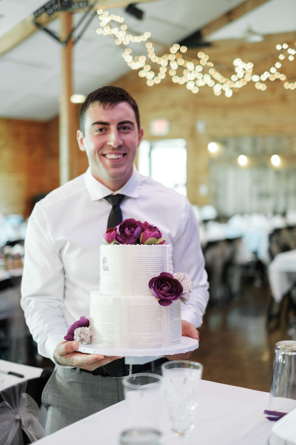 Groom holding Harry Potter themed wedding cake before placing it at head table at WIlliams Tree Farm wedding in Roscoe Illinois