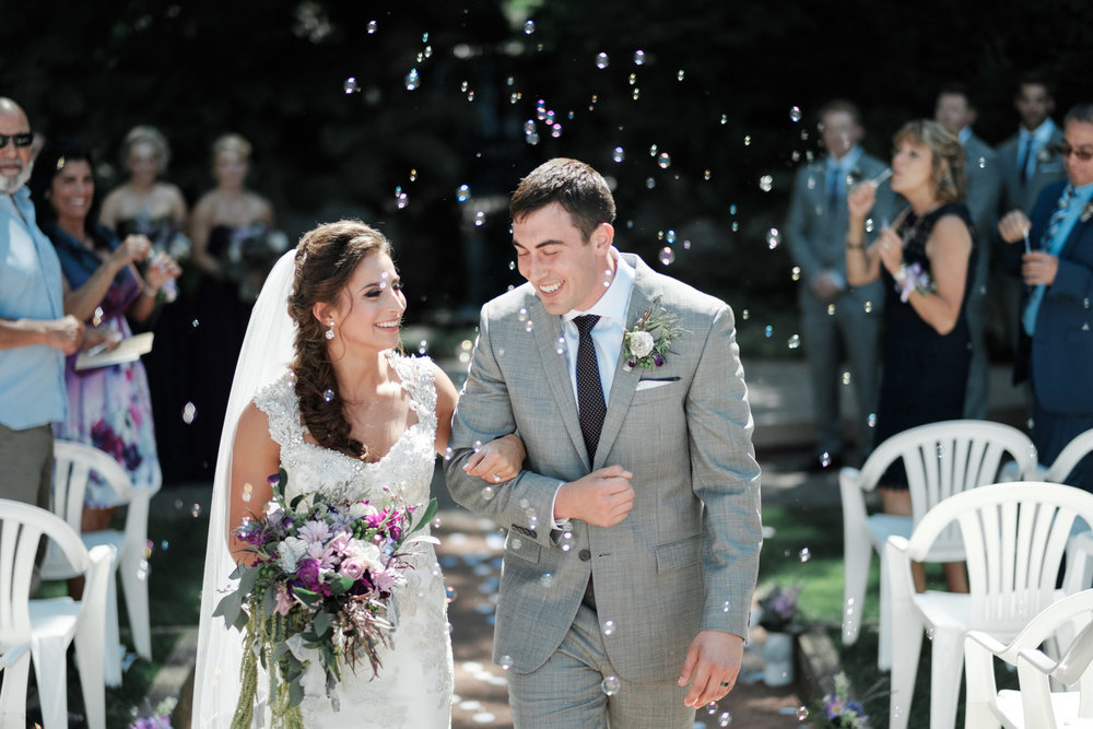 Bride and groom smiling and walking under bubbles at their Williams Tree Farm Wedding