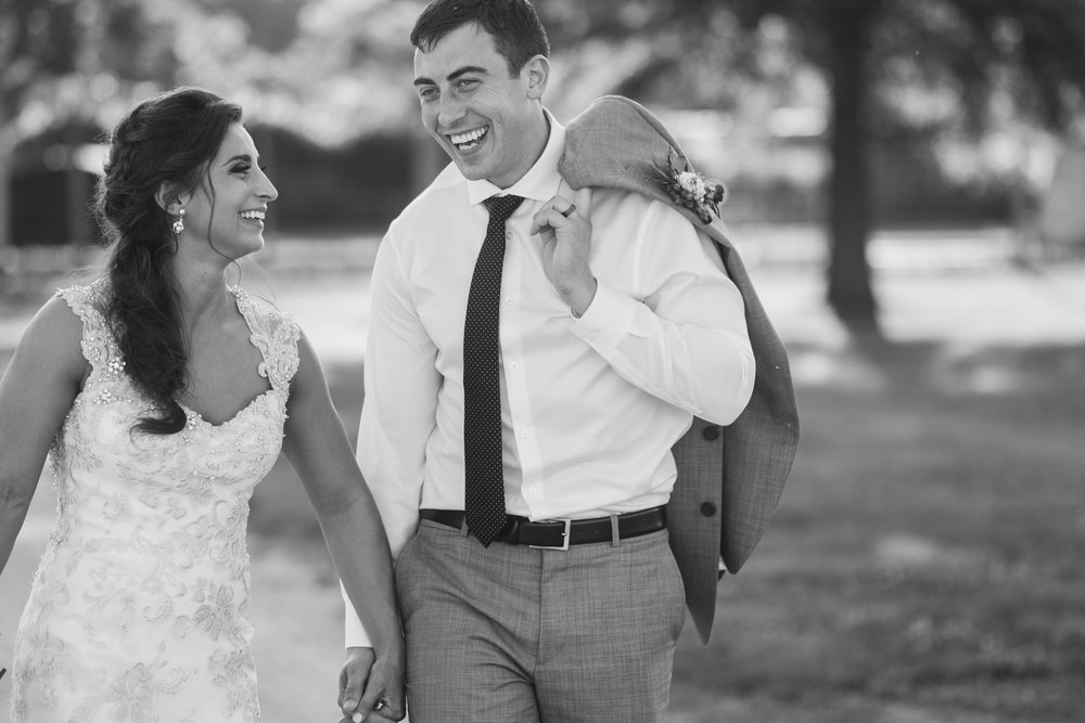 black and white photo of crossfit couple, smiling and laughing while walking at williams tree farm in rockton, illinois