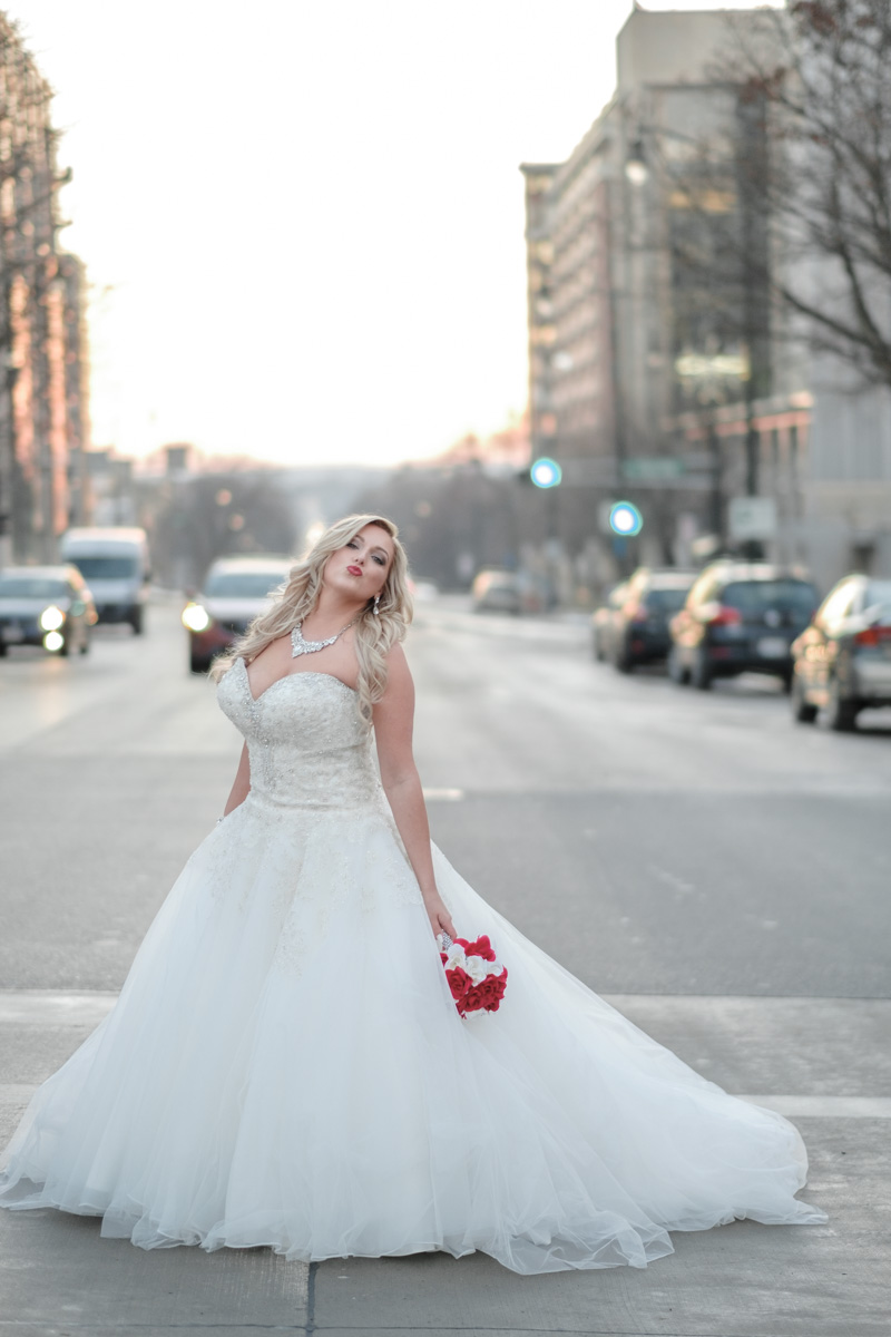 bride posing in middle of road in Madison Wisconsin blowing a kiss at the camera in front of Capital Building