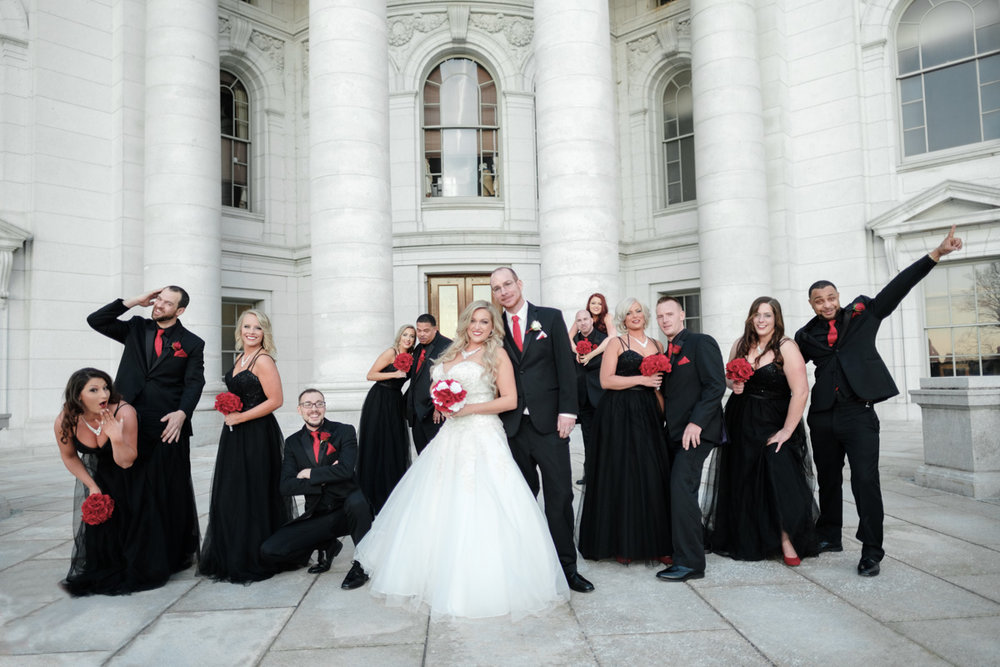 Wedding party in black suits and dresses with red flowers having fun in photo with bride and groom