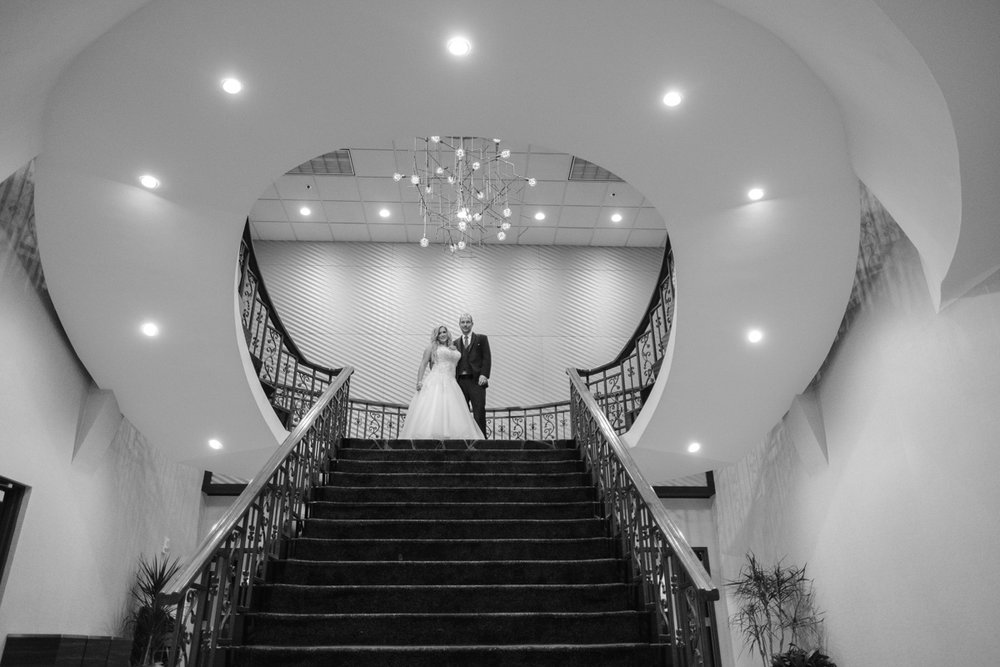 Black and white photo of bride and groom atop a spiral staircase in Madison Wisconsin