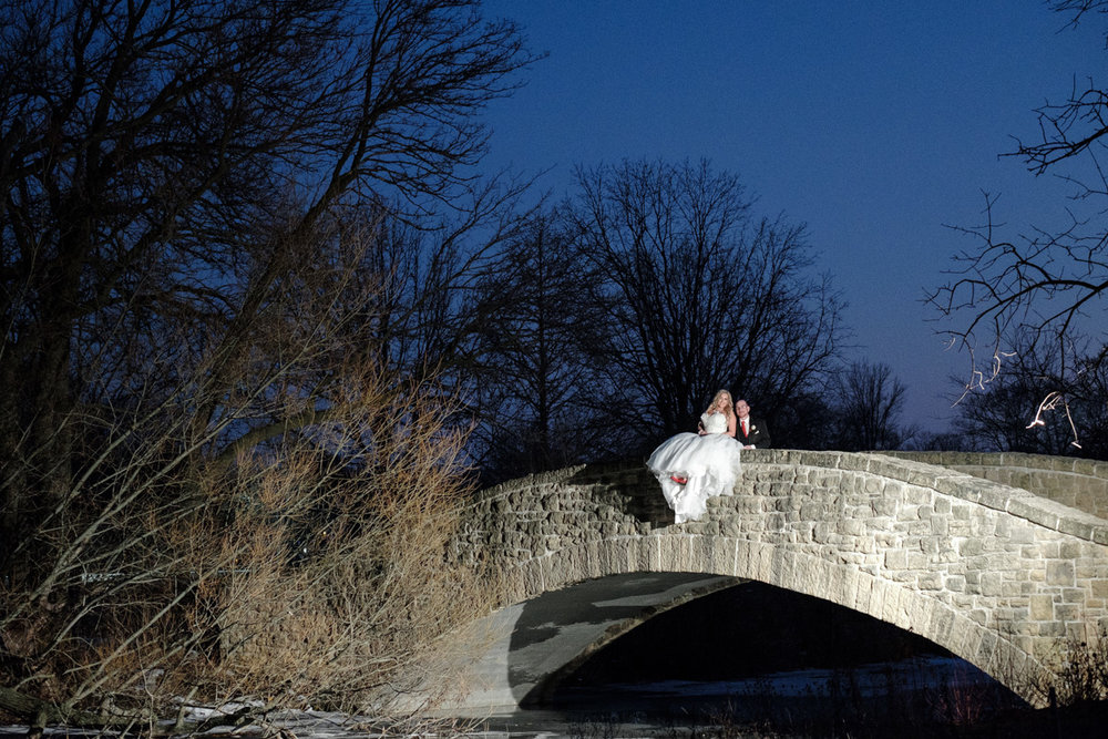 Night photo of bride sitting on the railing of a bridge snuggling with her husband.