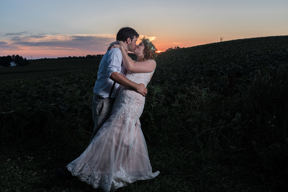 Groom dipping bride for a kiss at sunset overlooking a field at the barn at trinity peak in oconomowoc, wisconsin