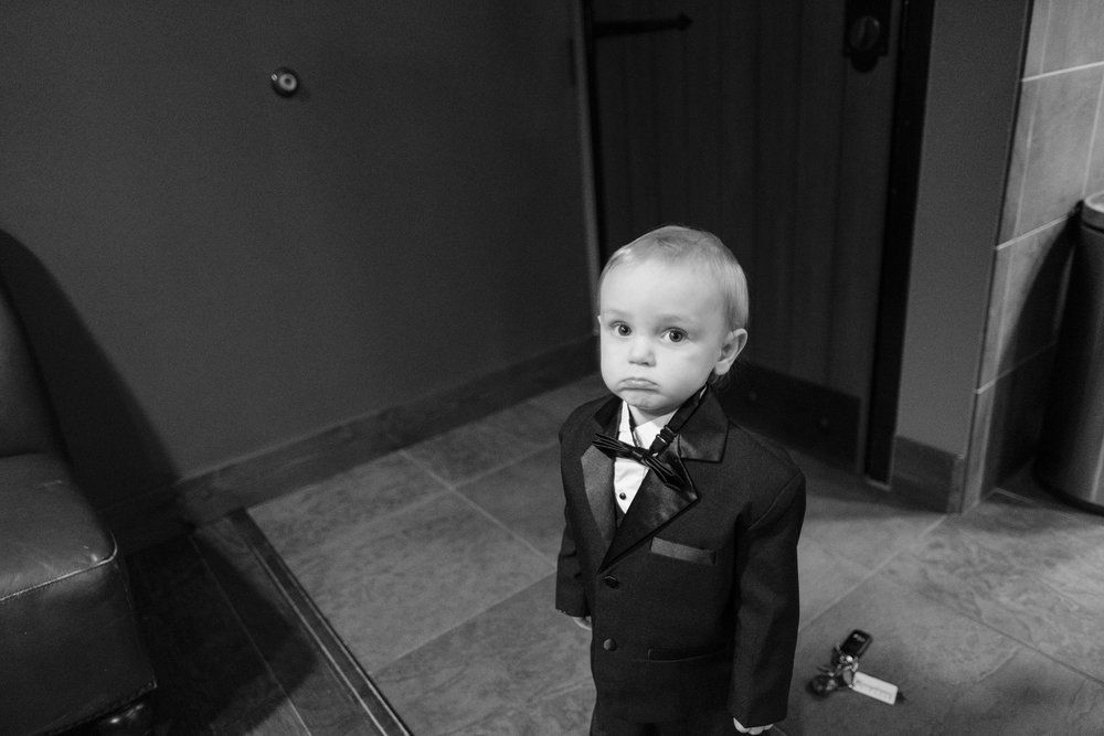 groom son  in tux looking on while watching his father get ready at the pavilion at orchard ridge farms