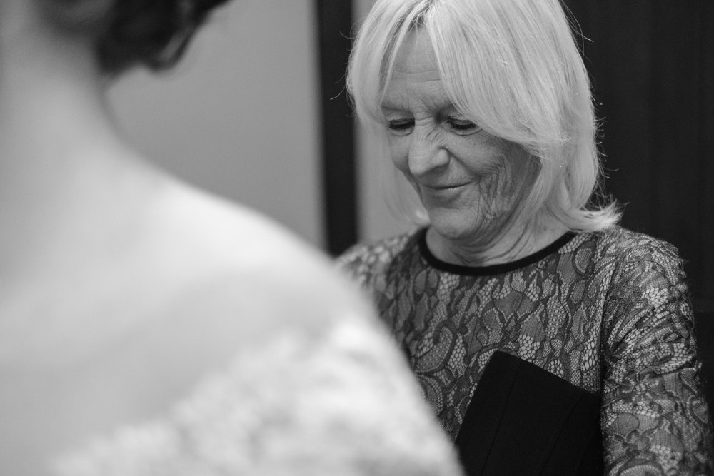 Brides mom helping get her into dress at the pavilion at orchard ridge farms.