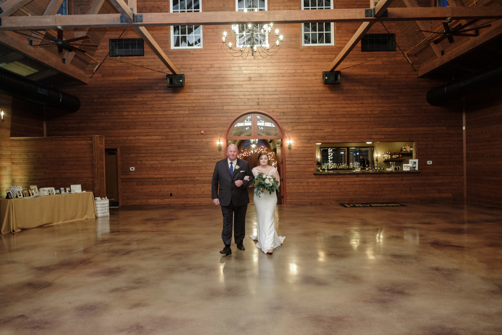 Bride walking into her wedding escorted by her father at the pavilion at orchard ridge farms in rockton, illinois