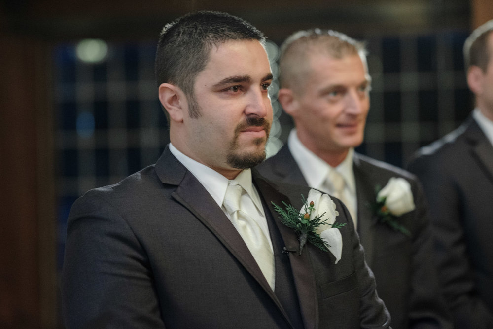 Groom beginning to cry seeing his bride walking into their wedding at the pavilion at orchard ridge farms