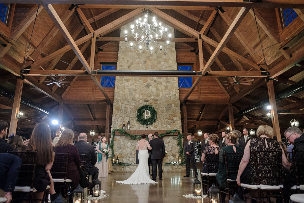 Winter wedding ceremony in front of floor to ceiling limestone fireplace at the pavilion at orchard ridge farms