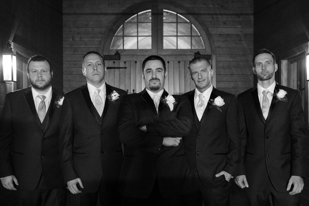black and white photo of groom and groomsman standing in front of entrance to barn at the pavilion at orchard ridge farms in rockton, illinois
