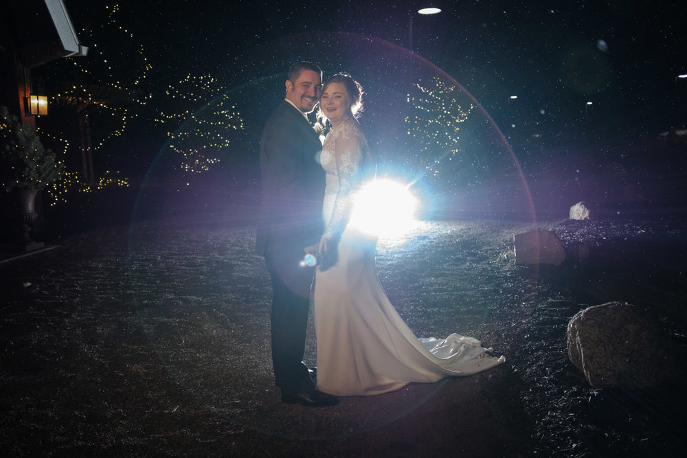 Newly married couple in front of Pavilion at ORchard Ridge farms back lit with christmas lights and falling snow illuminated in background