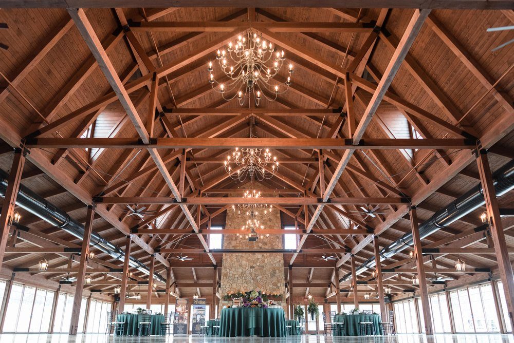 Interior view of the Pavilion with stone fireplace, walls of windows and chandeliers with beams above