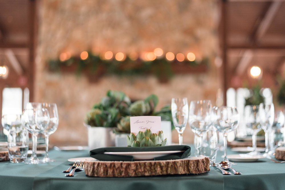 Minty green table setting by event floral with wood slabs and succulents with fireplace mantle lit candle light