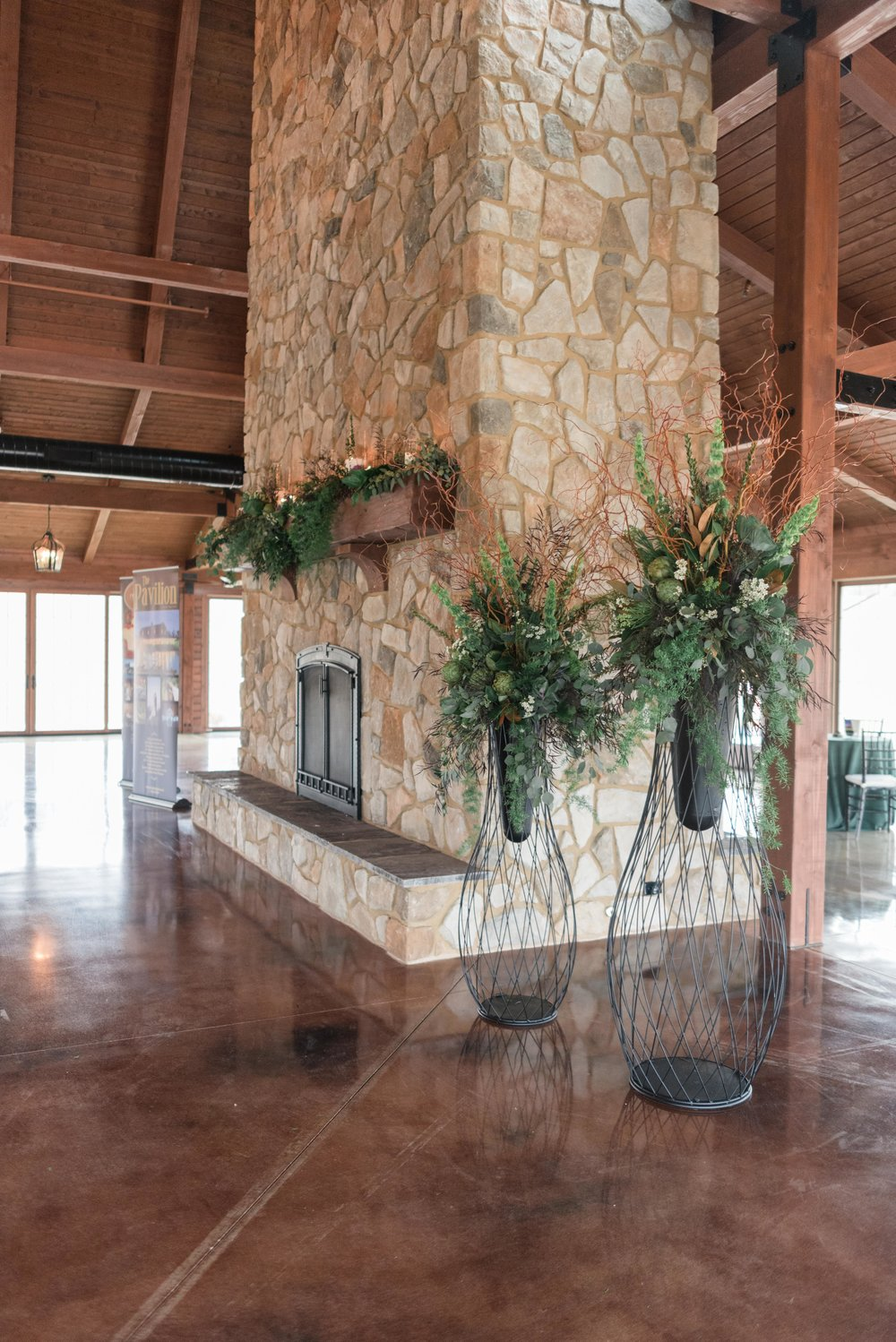 Florals by Event Floral frame the floor to ceiling stone fireplace at the Pavilion at ORchard Ridge Farms