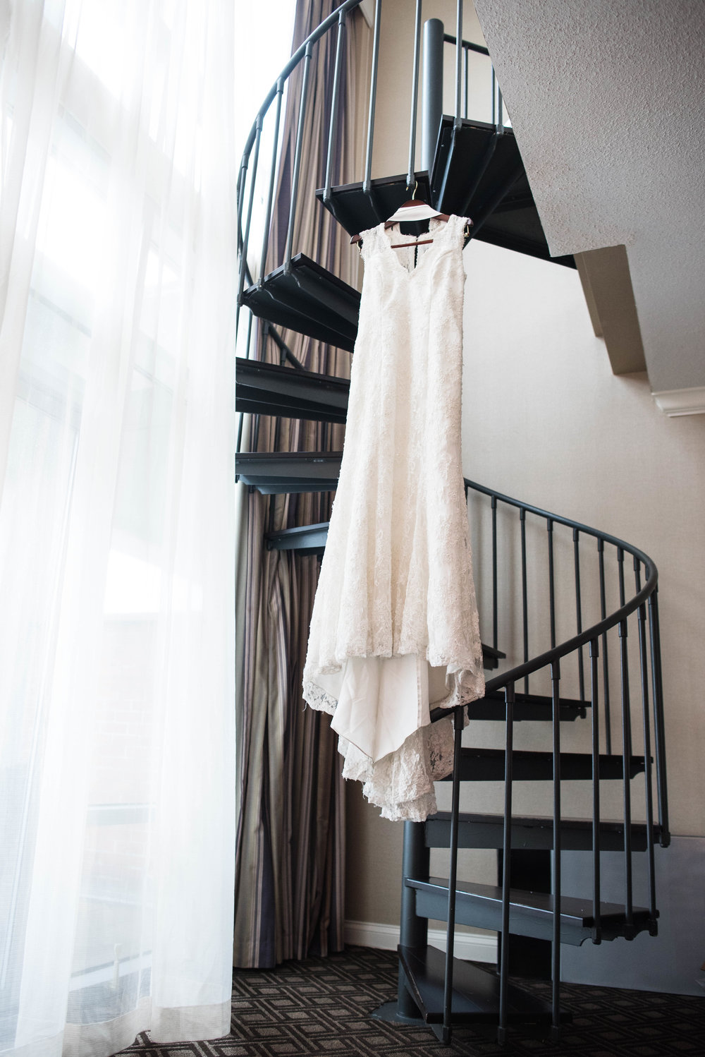 Bride dress hanging from spiral staircase at omni severin hotel