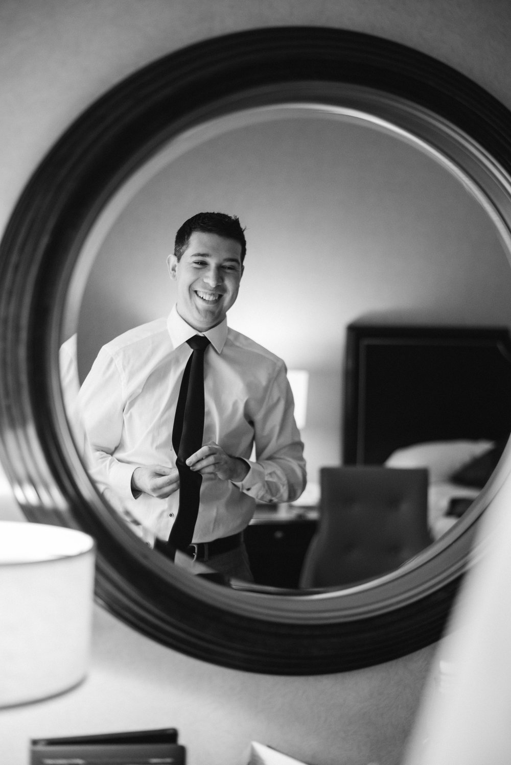 Reflection of groom in mirror getting ready and tying tie at omni severin hotel in Indianapolis, Indiana.