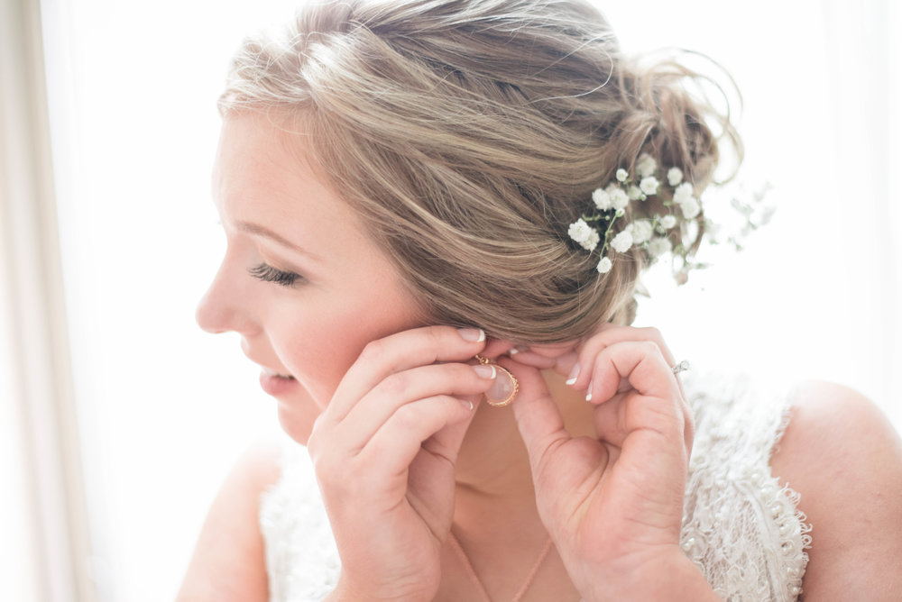 bride getting ready putting earring in at the omni severin hotel in indianapolis, Indiana