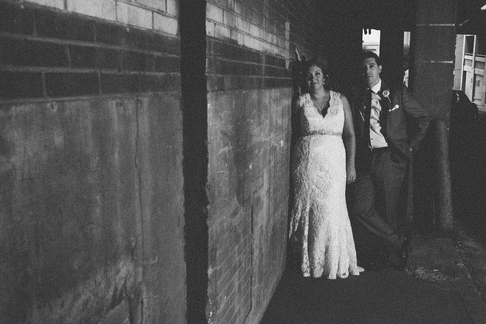 Black and white portrait of bride and groom in alley way of Indianapolis, Indiana