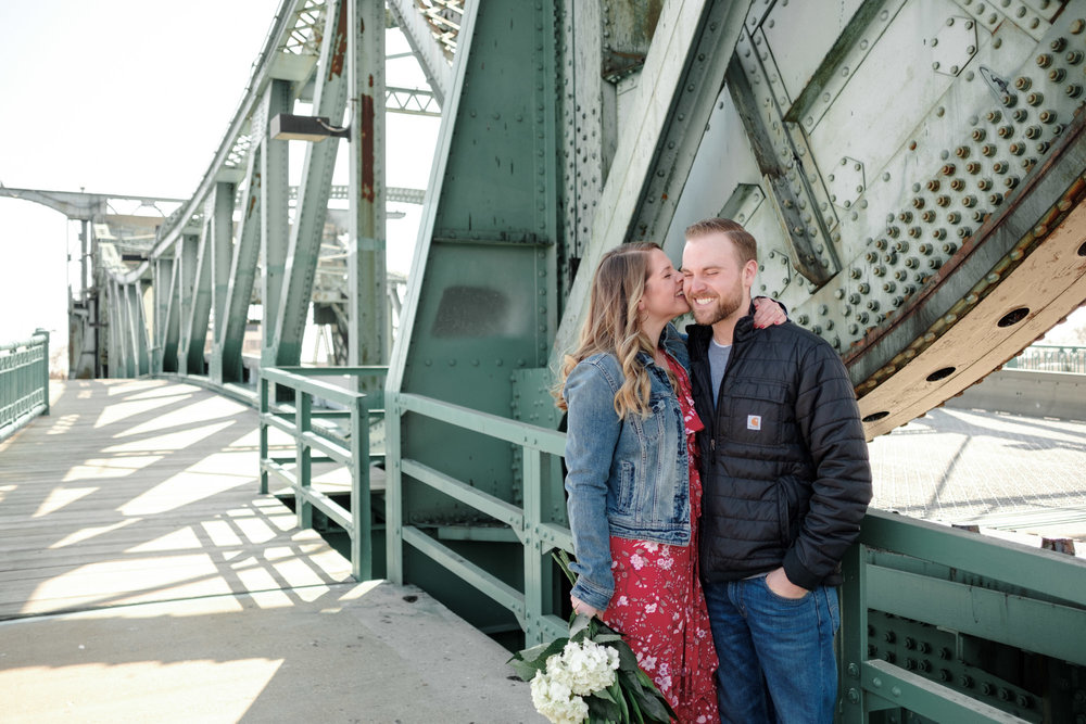 Couple kissing on steel bridge in downtown joliet during their engagement session