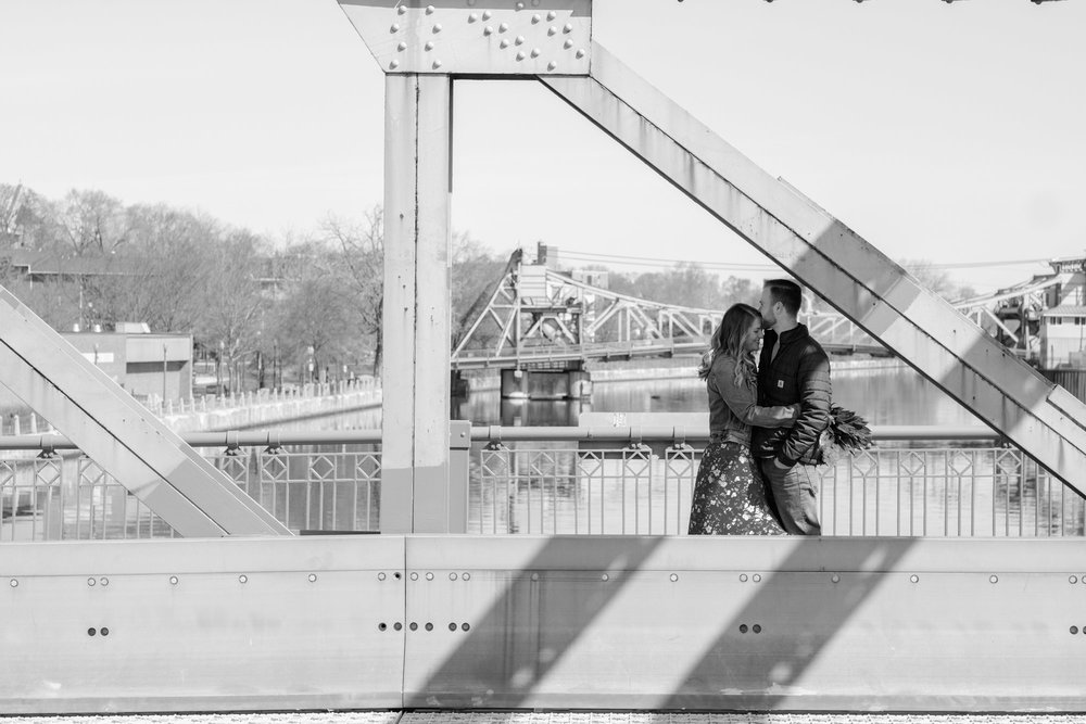 black and white photo of couple embracing and kissing on a bridge overlooking river and casino in Joliet, Illinois