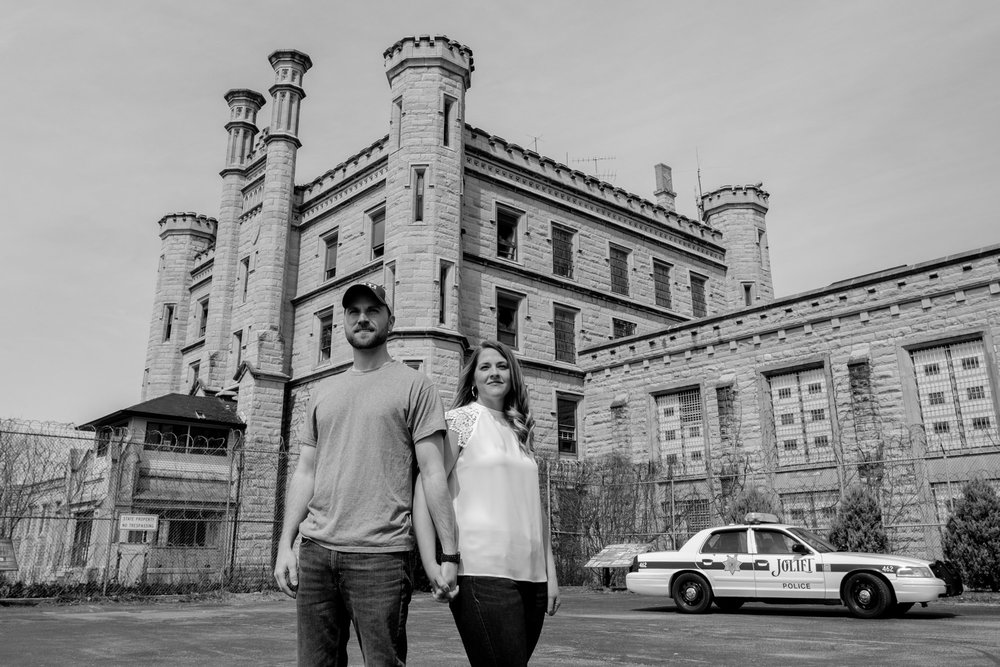 Engagement photo with police car and old joliet prison in background