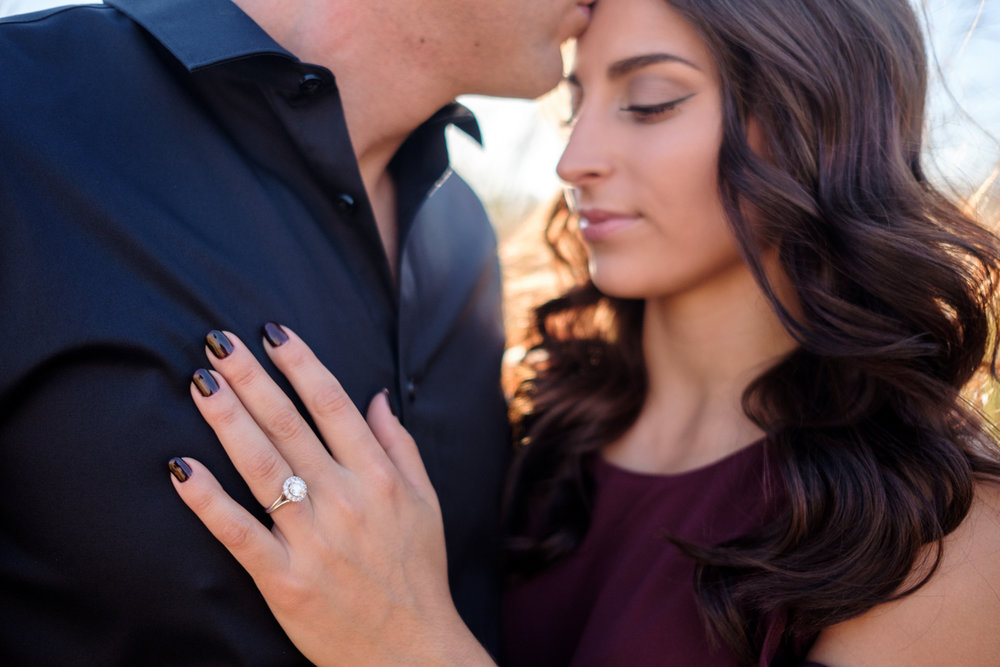 groom kissing her head with engagement ring focus resting on his chest.