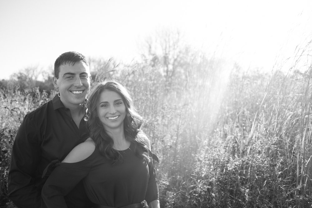 black and white photo of couple in tall grass in rock cut state park during their engagement session